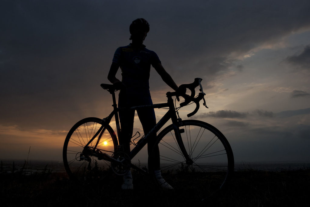 Silhouette of a biker with his bicycle at sunset